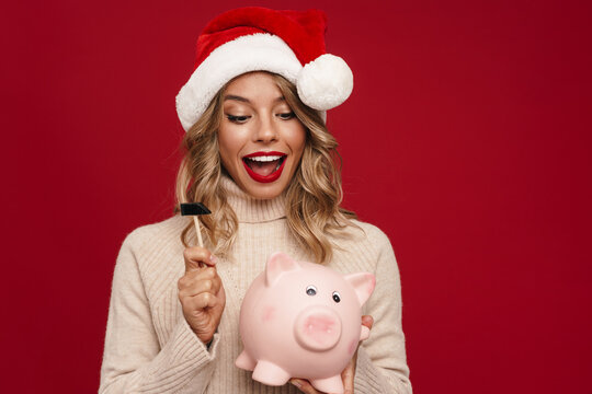 Beautiful delighted girl in Santa Claus breaking piggy bank
