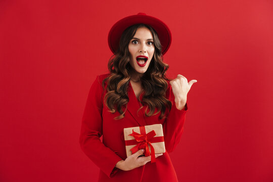 Surprised beautiful woman pointing finger aside and holding gift box