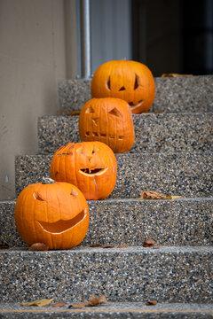 Halloween- selbst geschnitzte Kürbisköpfe schmücken eine Treppe vor einer Haustüre