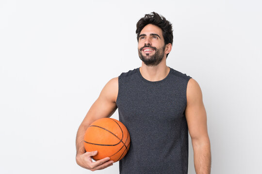 Basketball player man with beard over isolated white background looking up while smiling