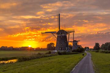Wall Mural - Historic wooden windmills orange sunset