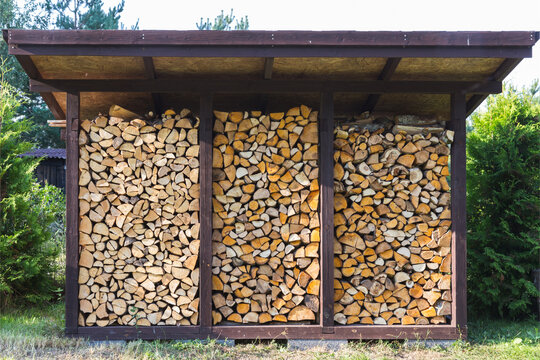 They prepare firewood for heating in winter. Firewood is neatly stacked under the roof of the shed for heating.