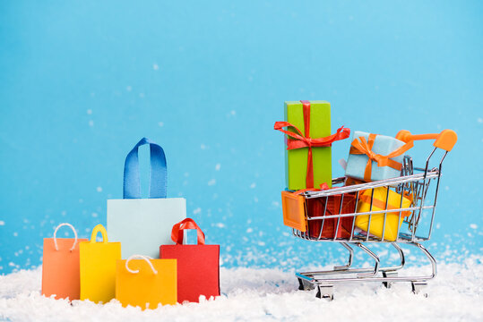 Tiny paper bags near trolley with bunch of little gifts on blue background, new year concept