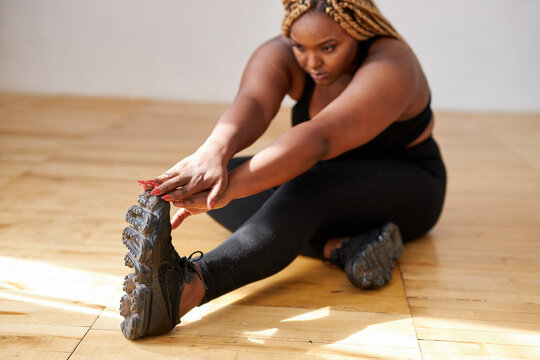 chubby african american woman do exercises sitting on the floor, plus size black female model in sportswear engaged in fitness, eant to loss weight