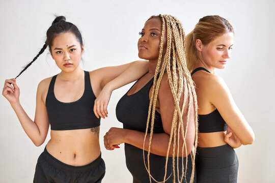 young group of mixed race fitness team stand isolated on white background, different ethnicity models portrait. body positive, sport as lifestyle.
