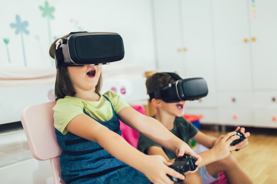 Little kids in virtual reality headsets playing video game at home