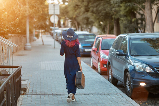 Stylish female walking down street with suitcase and hat. Long road ahead and cars. Travel time and new places concept