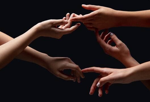 Loving. Hands of people's crows in touch isolated on black studio background. Concept of human relation, community, togetherness, symbolism. Light and weightless touching, creating one unit.