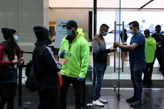 Customers and staff wear protective masks at the entrance of an Apple Store in Sydney