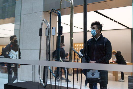 A customer wearing a protective mask looks at an iPhone 12 Pro display inside an Apple Store in Sydney