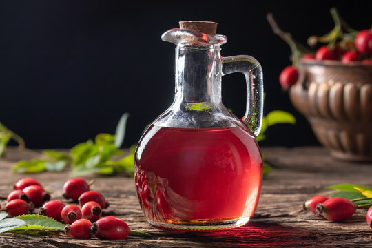 A bottle of rose hip seed oil with fresh rose hips