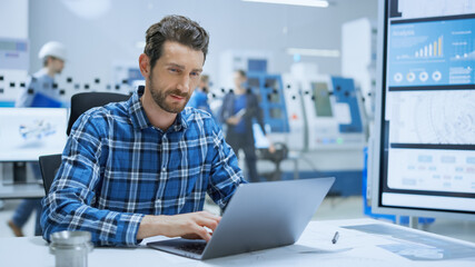 Modern Industrial Factory: Portrait of Industry Engineer Sitting at His Desk, Working on Laptop, Analyzing Mechanism and Blueprints. Background Functional Manufactory with Working on CNC Machinery