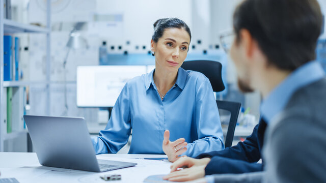 Modern Factory Office Meeting Room: Confident Female Project Manager Talks to Diverse Team of Engineers, Businesspeople and Investors Sitting at the Conference. Manufacturing Facility Optimization