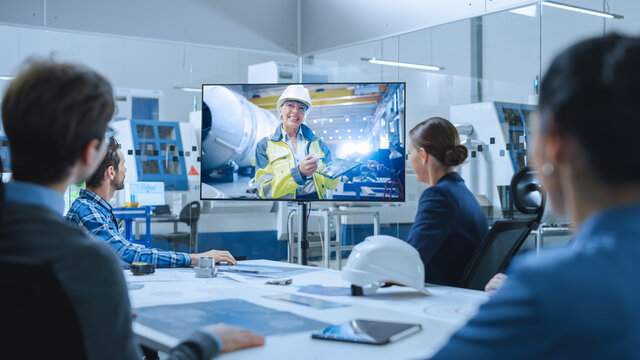 Diverse Group of Specialists, Managers in the Factory Office Meeting Room, Have Conference Video Call with Factory Chief Female Engineer, She Talks about Production Growth, Uses Tablet Computer