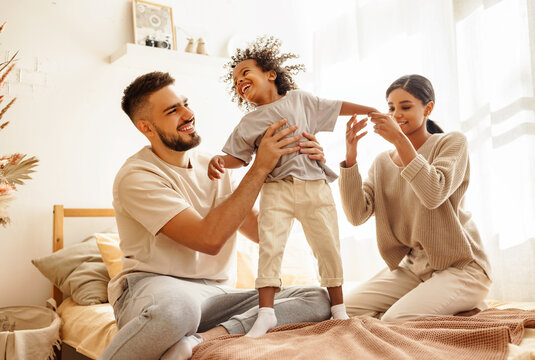 happy diverse family mom, dad and child  laughing, playing and jumping   in bed   at home.