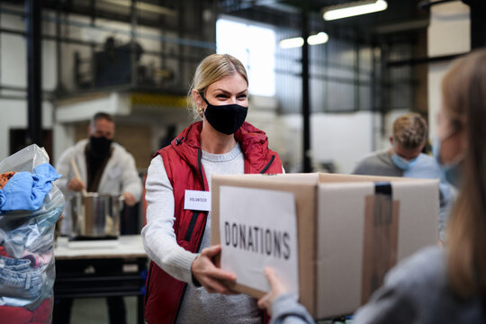 Volunteers working with food and clothes in community charity donations center