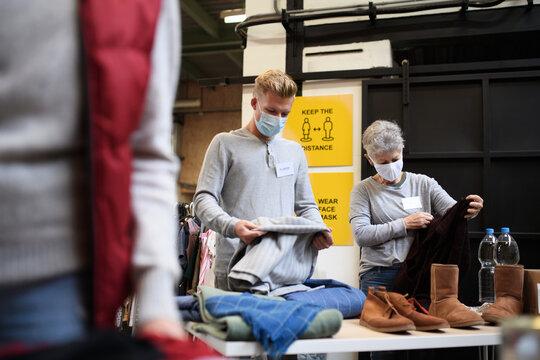 Volunteers sorting out donated clothes in community charity donation center, coronavirus concept.