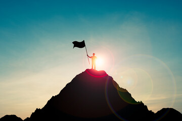 Silhouette of businessman holding flag on the top of mountain with over blue sky and sunlight. It is symbol of leadership successful achievement with goal and objective target.