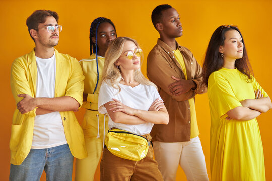 portrait of individual people of different races standing separately looking away, wearing trendy yellow wear and posing isolated on yellow background in studio. people diversity, fashion concept