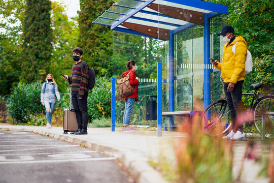 Young people with smartphones on bus stop outdoors in town. Coronavirus concept.