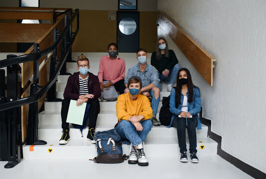 Front view of young students with face masks back at college or university, coronavirus concept.