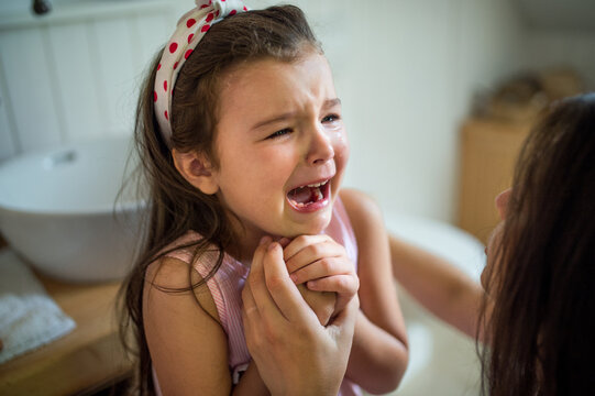 Crying small girl with unrecognizable mother indoors, loosing baby tooth.