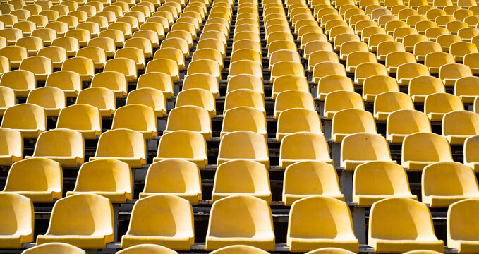 seats of tribune on sport stadium. empty outdoor arena. concept of fans. chairs for audience. cultural environment concept. color and symmetry. empty seats. modern stadium. yellow tribunes