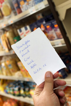 Hand holding a shopping list (Germany)