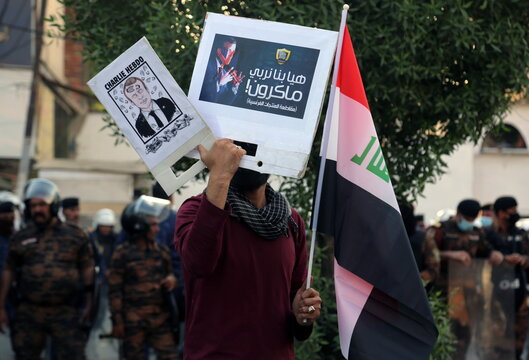 A man carries an Iraqi flag and poster of French President during a protest against the publications of a cartoon of Prophet Mohammad in France and Macron's comments, outside the French embassy in Baghdad