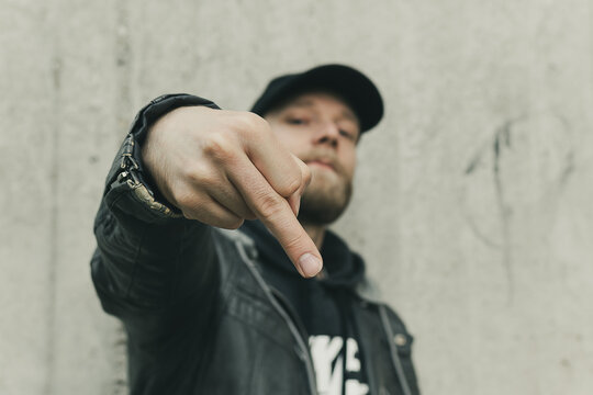 Portrait of a young angry man with black t-shirt. Leather jacket and cap looking at the camera and showing the middle finger. Shot outdoors in front of a concrete wall.