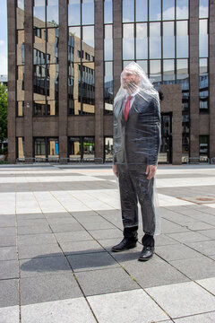 a man in a suit is standing in a plastic bag in front of an office building