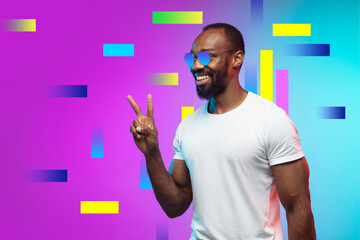 Greeting. Portrait of african-american man in bright colors. Trendy neon lighted background with copyspace for ad. Modern design. Contemporary art collage. Inspiration, mood, creativity concept.