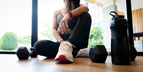Woman exercise workout in gym fitness breaking relax after training sport with dumbbell and water bottle.