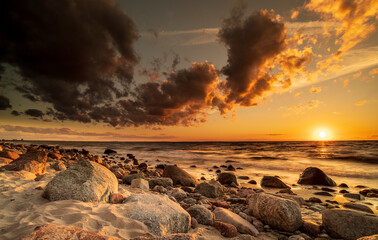 Obraz Sunset by the sea. Stones, sand and the sea illuminated by the rays of the setting sun. - fototapety do salonu