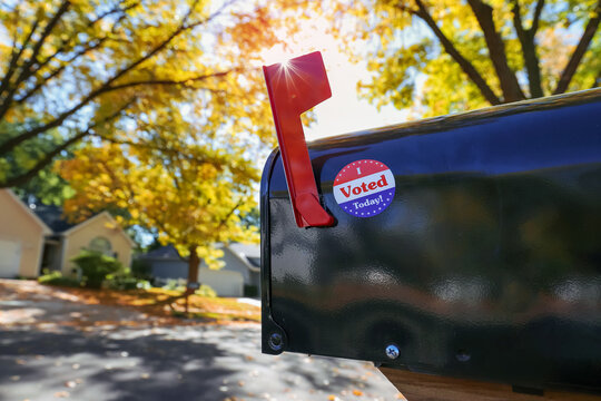 """Mailbox with an """"I voted today"""" sticker on it with sun flare behind flag, absentee voting through the mail"""