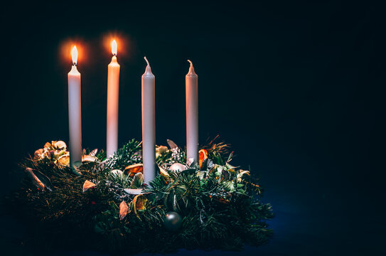 two advent candles burning on black background