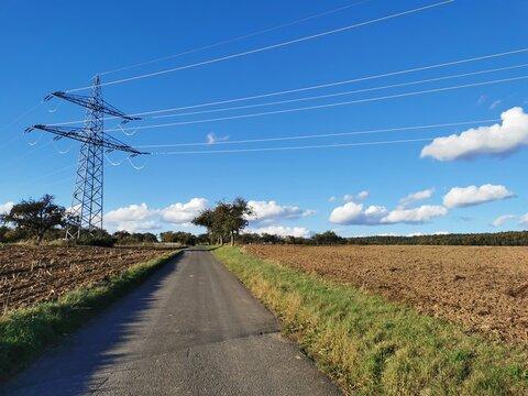 Hochspannungsleitung über einem Feldweg