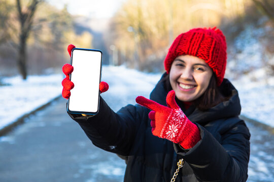 young smiling woman in winter outfit holding phone with white blank empty screen