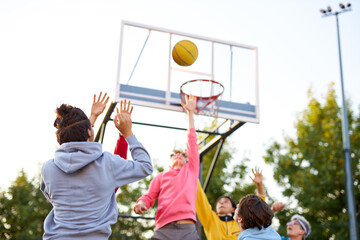 slam dunk. young caucasian basketball players, boys throwing ball into basketball hoop at...