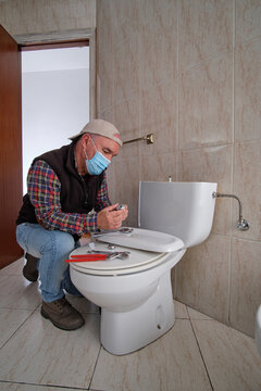 Plumber repairing a toilet with a mask