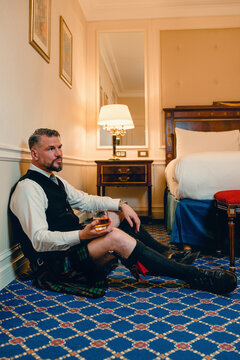 handsome mature courageous stylish man (gay) scotsman in kilt drinking whiskey on the floor in fancy hotel room. Style, fashion, lifestyle, culture, travel, ethnic concept.