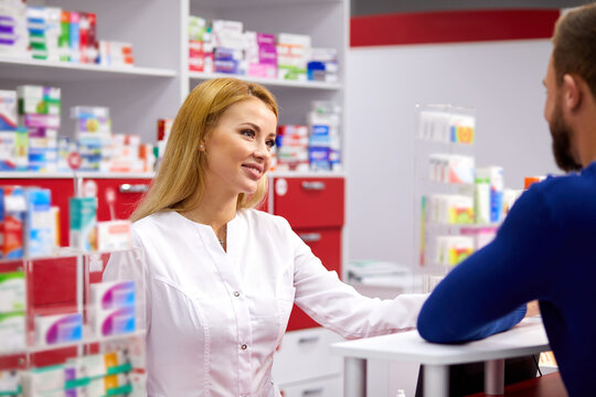 male customer having a discrete talk with druggist in pharmacy, ask for advice, pharmacist woman help, ask for symptoms