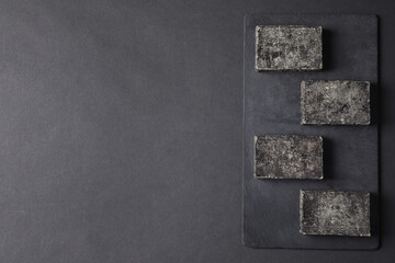 Wall Mural - Natural tar soap on black table, flat lay. Space for text