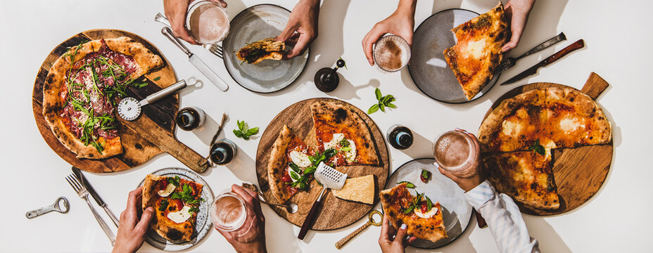 Pizza party for friends. Flat-lay of various pizzas, lager beer and peoples hands with pizza slices and glasses over white table background, top view. Fast food, comfort food, Italian cuisine concept