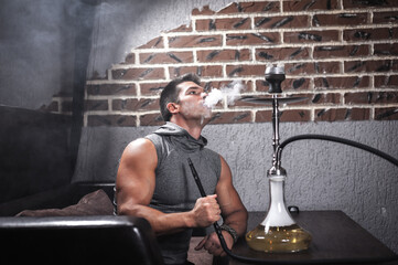 Sexy man relaxes in a hookah in night club.