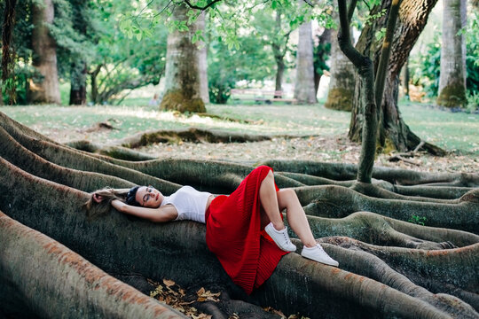 Young woman lying on root in park