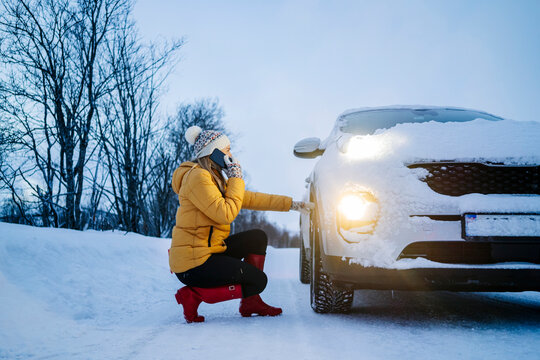 Mature woman talking over smart phone while crouching car on snow covered land