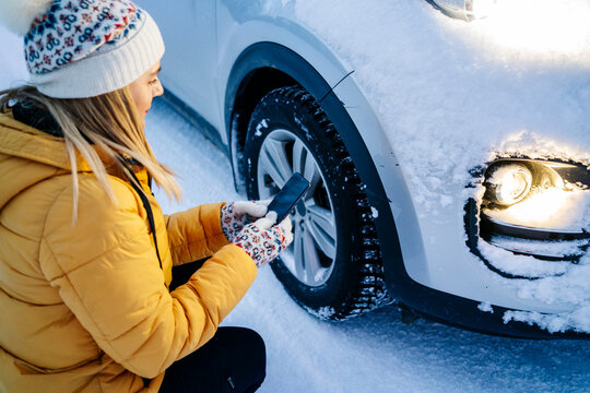 Mature woman using mobile phone while crouching by snow covered car