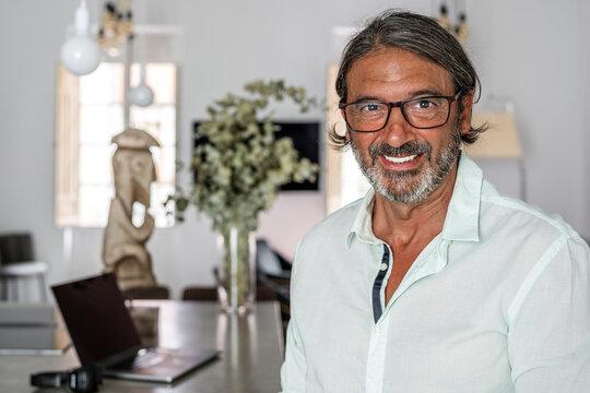 Smiling man wearing eyeglasses while standing at home