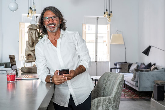 Smiling man using smart phone while standing by counter at home